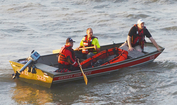 WARREN DILLAWAY / Star Beacon<br /> RESCUE WORKERS in a Geneva Fire Department boat look for an apparent missing swimmer along Lake Road West in Saybrook Township Friday evening.