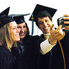 WARREN DILLAWAY / Star Beacon<br /> LISA LEHMAN of Cleveland (right) takes a picture of classmates Christy Mooney of Conneaut (left) and Mandy Mauger of Cortland Friday night before graduation at Kent State University-Ashtabula Campus.