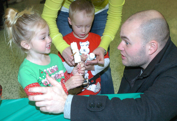 WARREN DILLAWAY / Star Beacon<br /> PAYTON WOODRING, 3, of Ashtabula proudly works on her marshmallow snowman with Nick Baliore (right) of Ashtabula as Parker Dewees, 3, of Ashtabula, works on his craft at the same time.
