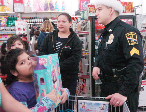 WARREN DILLAWAY / Star Beacon<br /> STEVE GERICS, president of the Conneaut Fraternal Order of Police Lodge 51, talks with Garza family Saturday morning at the Conneaut Kmart during the union's annual Shop with a Cop program. Abigail Garza (front left) holds her present tightly as her sister Brianna, 4, and mother Dara watch.