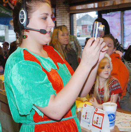 WARREN DILLAWAY / Star Beacon<br /> CASSANDRA CUNNINGHAM takes a picture of a bicycle winner Saturday during a Christmas party at Tony's Hot Dog House in Ashtabula.