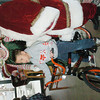 WARREN DILLAWAY / Star Beacon<br /> ZACHARY MILLARD, 9, of Ashtabula, poses with Mr. and Mrs. Claus after winning a bicycle Saturday at Tony's Hot Dog House in Ashtabula.