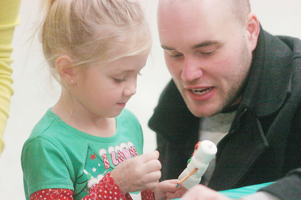 WARREN DILLAWAY / Star Beacon<br /> NICK BAGLIORE of Ashtabula helps Payton Woodring, 3, also of Ashtabula, make a marshmallow snowman Saturday morning during Breakfast with Santa at Edgewood High  School.