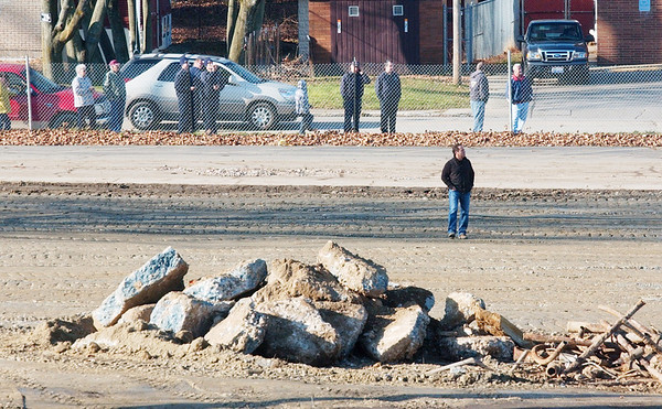 WARREN DILLAWAY / Star Beacon<br /> COSMO IAMURRI, owner of Pro Quality Land Developoers) watches his employees demolish a 135 foot smokestack on the site of the former Ashtabula High School.