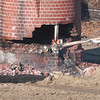 WARREN DILLAWAY / Star Beacon<br /> A Pro Quality Land Development workers uses a two by four to knock wooden support beams from the base of a 135 foot smokestack on the site of the former Ashtabula High  School Saturday morning. The technique was used to help bring down the historic smokestack.