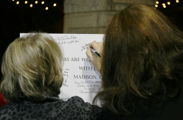 MARGIE NETZEL / Star Beacon<br /> TWO WOMEN sign a poster for the victims of the Sandy Hook Elementary shooting in Connecticut. The vigil, held Sunday night in Madison square, was organized by Behm Family Funeral Homes and Crematory.