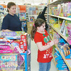 WARREN DILLAWAY / Star Beacon<br /> SHERRIE DOUGLAS (left), wife of Geneva-on-the-Lake police officer Randy Douglas, helps Penny Gonzales, 8, during a Saturday morning Shop with a Cop program at the Wal Mart in Ashtabula Township.