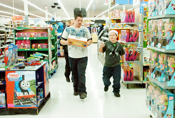 WARREN DILLAWAY / Star Beacon<br /> EDDIE TACKETT (left) helps his nephew Hayden Wilson, 10, during a Saturday morning Shop with a Cop program at the Wal Mart in Ashtabula Township.