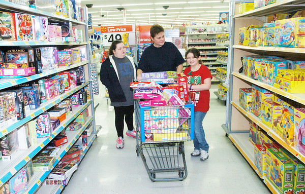 WARREN DILLAWAY / Star Beacon<br /> SHERRIE DOUGLAS (center), wife of Geneva-on-the-Lake police officer Randy Douglas, helps  Anastasia (left) Gonzales, 10, and Penny Gonzales, 8, during a Saturday morning Shop with a Cop program at the Wal Mart in Ashtabula Township.