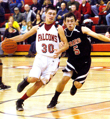WARREN DILLAWAY / Star Beacon<br /> LUCAS HITCHCOCK (30) of Jefferson drives to the basket with Girard defender Evan Standohar (5) close behind Friday night at Jefferson