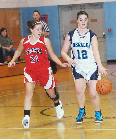WARREN DILLAWAY / Star Beacon<br /> MACKENZIE STENROOS (12) of St. John dribbles up court with Badger's Cheyanne Dickson defending (21) on Saturday at Mahoney Gymnasium in Ashtabula.