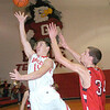 WARREN DILLAWAY / Star Beacon<br /> ZAK SWEAT of Geneva shoots as Jefferson's David Chase defends Tuesday night at Geneva.
