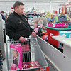 WARREN DILLAWAY / Star Beacon<br /> LT. TERRY MOISIO Jr. of the Ashtabula County Sheriff's Department Lodge 106 checks out presents for foster children Saturday during the annual Shop with a Cop program at Super Kmart in Ashtabula Township Saturday morning.