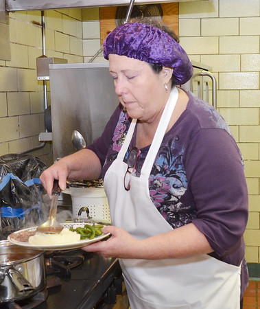 WARREN DILLAWAY / Star Beacon<br /> BOBBIE EASTMAN,  director of the Good Karma Kitchen at St. Joseph Church in Ashtabula, prepares meals during the opening day of the kitchen.