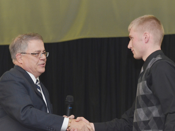 WARREN DILLAWAY / Star Beacon<br /> MARK ANDREWS presents the Warren G. Andrews Memorial Scholarship Award to Jake Vormelker of Grand Valley on Monday evening at Our Lady of Peace Community Center in Ashtabula during the Ashtabula County Touchdown Club Awards Dinner.
