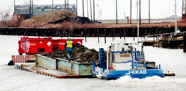 WARREN DILLAWAY / Star Beacon<br /> A BARGE hauling dredging material from the Ashtabula River dredging site moves north on the river Monday afternoon.