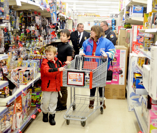 WARREN DILLAWAY / Star Beacon<br /> MICHELLE PUDNEY shops with Dustin Bixler, 6, (front left) and Kenny Griggs during the Conneaut Shop with a Cop program at the Big Kmart store Saturday morning.