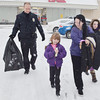 WARREN DILLAWAY / Star Beacon<br /> CONNEAUT PATROLMAN Joe Schorr helps Kim Campbell and her daughters Amyah, 11, and Kylah, 7, (center front) to their car after  the Conneaut Shop with a Cop program at the Big Kmart store Saturday morning.
