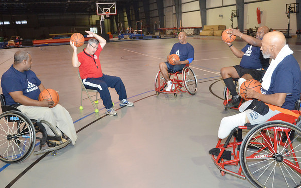 WARREN DILLAWAY / Star Beacon<br /> STEVE GLATCH, mens and womens wheelchair basketball coach at Edinboro University, (second from left) demonstrates a ball handling drill on Saturday during a wheelchair basketball clinic at Spire Institute in Harpersfield Township.