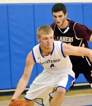 WARREN DILLAWAY / Star Beacon<br /> JAKE VORMELKER (4)  of Grand Valley dribbles by Quintin Ratliff of Pymatuning Valley on Friday night in Orwell.