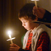 WARREN DILLAWAY / Star Beacon<br /> ZACHARY STAFFORD, 9, of Ashtabula, holds a lighted candle Christmas Eve at First Covenant Church in Saybrook Township.