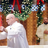 WARREN DILLAWAY / Star Beacon<br /> MICHAEL GARDNER raises the Word of God during Christmas Day Mass at Our Lady of Peace Mount Carmel in Ashtabula.