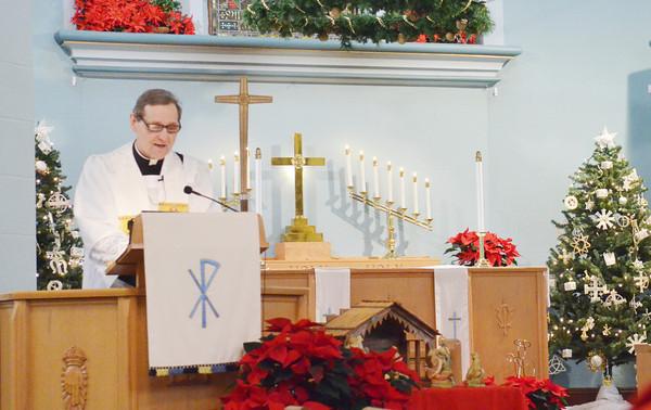 WARREN DILLAWAY / Star Beacon<br /> REV. MICHAEL MERANDA begins a Christmas Day church service at Messiah Lutheran Church in Ashtabula on Wednesday morning.