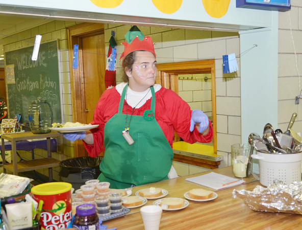 """WARREN DILLAWAY / Star Beacon<br /> """"DRAGON FLY"""" VANPELT prepares to serve Christmas dinner on Wednesday at Good Karma Kitchen at Our Lady of Peace St. Joseph's in Ashtabula."""