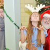 WARREN DILLAWAY / Star Beacon<br /> MAYLENE GONZALES, 12, sits on Santa's lap, played by her father Manny Gonzales, as Julia Downing, 10, of Ashtabula hides behind a pole at Good Karma Kitchen at Our Lady of Peace St. Joseph's on Wednesday.