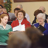 WARREN DILLAWAY / Star Beacon<br /> ANDREA TREDENT (lower left with arm in air) directs a choir and the congregation during a Christmas Day Mass at Our Lady of Peace Mount Carmel on Wednesday morning.