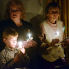 WARREN DILLAWAY / Star Beacon<br /> ANDREW CARROL, 8, of Geneva, and Tammy Napier (left) sing Silent  Night with Dolly  Matson and other worshippers on Christmas Eve at First Covenant Church in Saybrook Township.