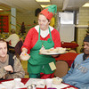 """WARREN DILLAWAY / Star Beacon<br /> """"DRAGON FLY"""" VANPELT (center) serves Joshua Crane (left) and Anthony Bowser Christmas dinner on Wednesday at Good Karma Kitchen at Our Lady of Peace St. Joseph's in Ashtabula."""