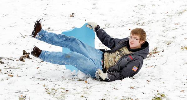 WARREN DILLAWAY / Star Beacon<br /> KEVIN THOMAS, 14, of Ashtabula, loses his sled at Lake Shore Park on Friday afternoon.