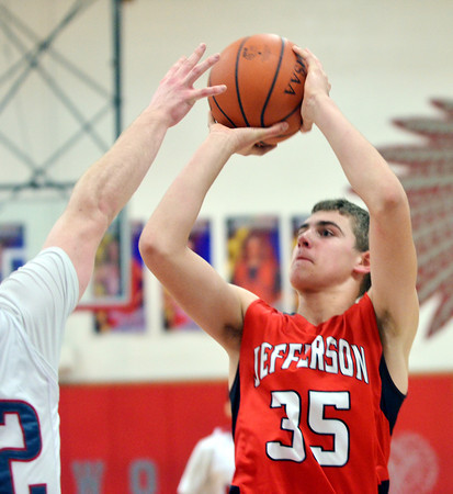 WARREN DILLAWAY / Star Beacon<br /> SAM HITCHCOCK of Jefferson prepares to release a shot as Anthony Monda of Edgewood defends on Friday night at Edgewood.