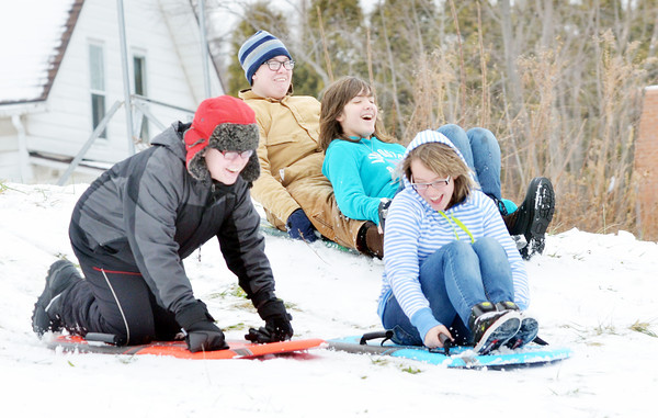 WARREN DILLAWAY / Star Beacon<br /> ALEX MOBLEY (far left), and his twin brother Donovan, both 15, go sled riding with Hailey Slocum, 11, (second from right) and Alexis Slocum, 14, (front right) at Skippon Park in Conneaut.