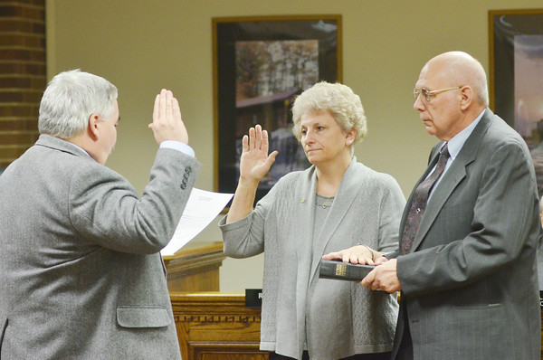 WARREN DILLAWAY / Star Beacon<br /> JOSEPHINE MISENER (center) takes the Ashtabula City Council oath of office from Ashtabula City Solicitor Mike Franklin (left) with husband Kenneth Misener holding the Bible on Monday night in Ashtabula City Council chambers.