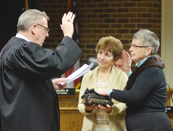 WARREN DILLAWAY / Star Beacon<br /> ALICE T. COOK (right) takes the Ashtabula City Council oath of office from Eastern County Court Judge Robert S. Wynn (left) with friend Celeste Corbissero holding the Bible on Monday night in Ashtabula City Council chambers.