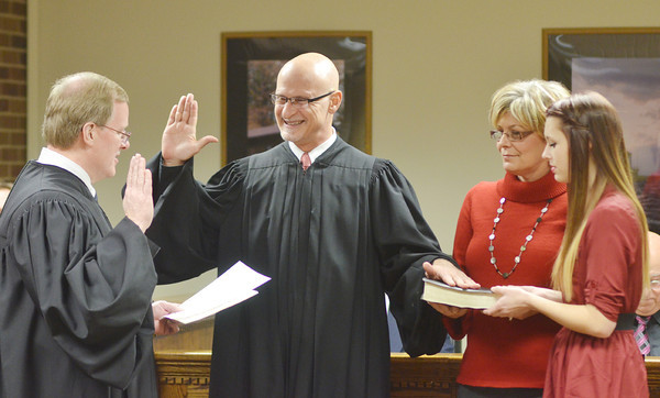 WARREN DILLAWAY / Star Beacon<br /> ASHTABULA MUNICIPAL Court Judge Albert Camplese takes the oath of office (facing) from Conneaut Municipal Court Judge Thomas Harris (left) as his wife Krysti Camplese and daughter Alex Johnson hold the Bible on Monday evening in Ashtabula City Council chambers.