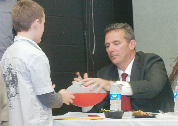 WARREN DILLAWAY / Star Beacon<br /> URBAN MEYER, St. John graduate and Ohio State football coach, signs an autograph Monday night during the Ashtabula County Touchdown Club Banquet at Mount Carmel Community Center.