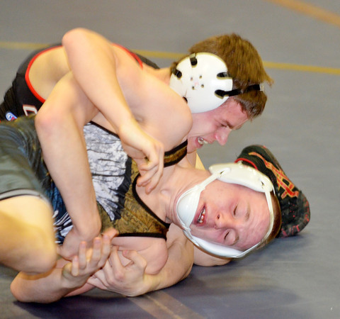 WARREN DILLAWAY / Star Beacon<br /> JUSTIN MASON (bottom) of Conneaut tries to escape the grasp of Mike Connick of Chardon on Thursday evening during a 132 pound bout at Conneaut.