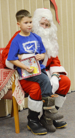 WARREN DILLAWAY / Star Beacon<br /> CHESTER ARCARO IV of Conneaut, 5,  sits on Santa's lap during the Conneaut Public Library Christmas party on Thursday evening.