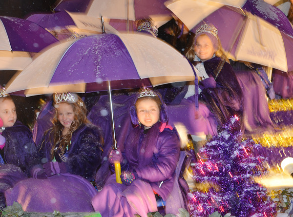WARREN DILLAWAY / Star Beacon<br /> MEMBERS OF the Grape Jamboree royalty try to stay dry while waiting for the Geneva Christmas Parade to start on Friday evening in Geneva.