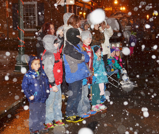 WARREN DILLAWAY / Star Beacon<br /> CHILDREN WATCH the Geneva Christmas Parade on South Broadway during a snowy Friday evening.