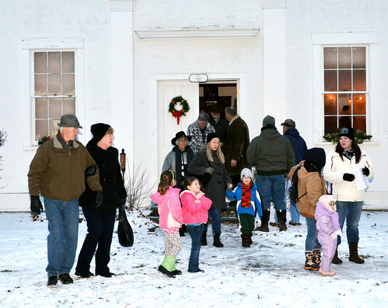 WARREN DILLAWAY / Star Beacon<br /> CAROL SINGERS leave the Church in the Wildwood at the Jefferson Depot Village on Saturday following a Christmas sing during the Old Fashioned Williasburg Christmas Celebration.
