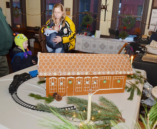WARREN DILLAWAY / Star Beacon<br /> NANCY GRUNAUER and her grandchildren Wyatt Clark, four months in pouch, and Kaleb Clark, 4, both of Conneaut, tour the Jefferson Depot Village Train Depot during the Old Fashioned Williamsburg Christmas in Jefferson on Saturday afternoon.