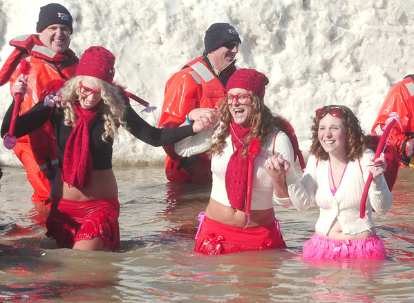 WARREN DILLAWAY / Star Beacon<br /> NICOLE BELUSO (left) of Cleveland, Daisy Hall of Jefferson and Josie Kmiec of Madison are all smiles while dashing through the water on Saturday during the Polar Bear Plunge at Geneva State Park's Breakwater Beach.