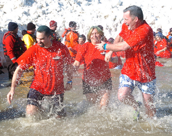 WARREN DILLAWAY / Star Beacon<br /> MEMBERS OF the Perkins family (from left) Tom, Laura and Ed, all of Senecaville, splash each other on the way out of Lake Erie during the Polar Bear Plunge at Geneva State Park Breakwater Beach Saturday.