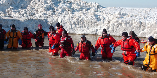 WARREN DILLAWAY / Star Beacon<br /> EMERGENCY WORKERS join hands to come out of the water following the Polar Bear Plunge on Saturday at Geneva State Park's Breakwater Beach.