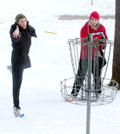 WARREN DILLAWAY / Star Beacon<br /> TRAVIS ISENBERG (left) putts on Saturday morning with Ben Markel looking on during the 2013 Ice Bowl at Lake Shore Park in Ashtabula Township.