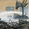 WARREN DILLAWAY / Star Beacon<br /> A CONNEAUT firefighter hoses down the remnants of the former General Alumninum building Tuesday morning after it burned Monday night in Conneaut.